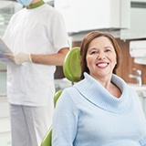 Woman in dental chair for implant-retained dentures