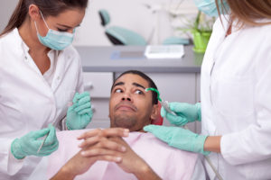 Scared man in dental chair with dentist and team members above him