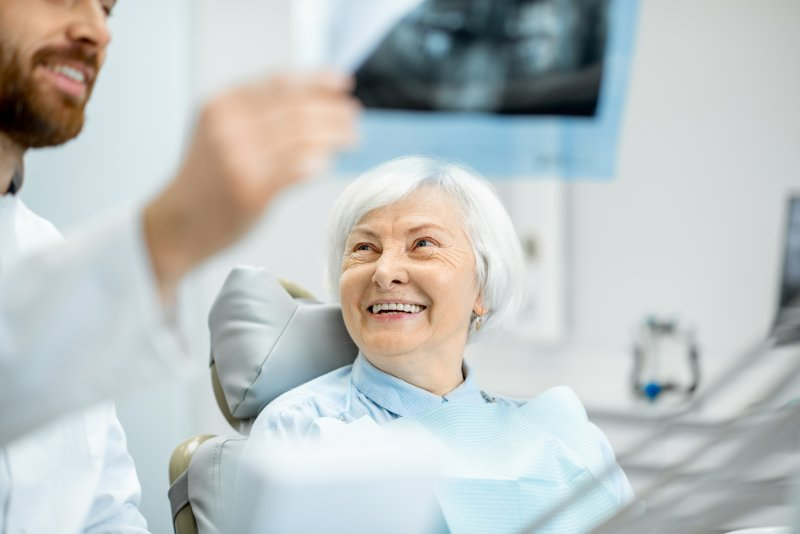 an older woman smiling at her dentist while he explains the process for receiving a dental implant in La Porte