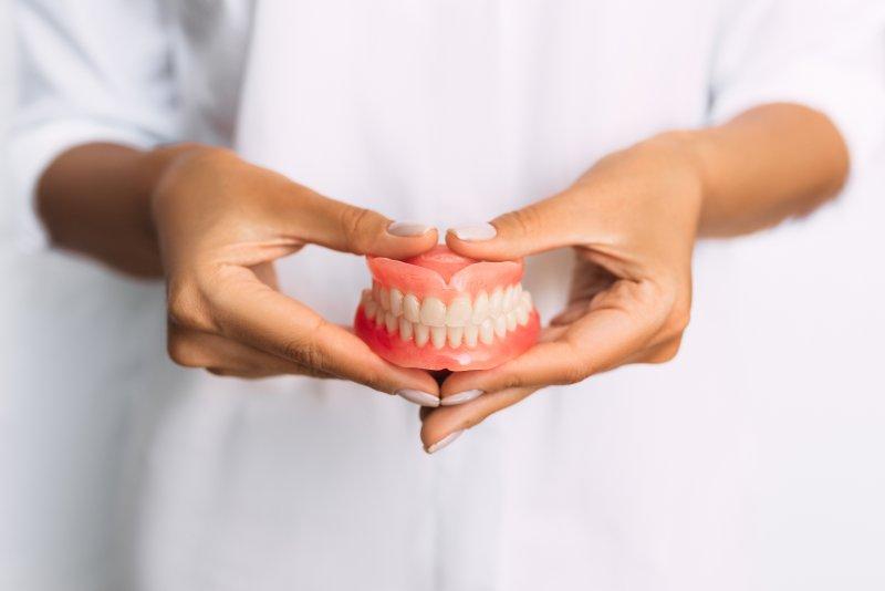 dentist holding dentures in hands